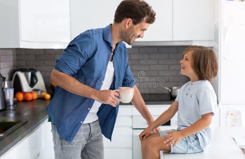 父亲和儿子在厨房里 库存图片