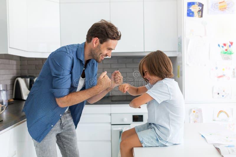 父亲和儿子在厨房里 免版税库存照片