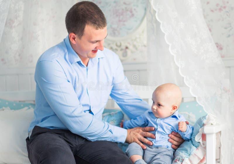 父亲和儿子在托儿所坐和使用 免版税库存照片