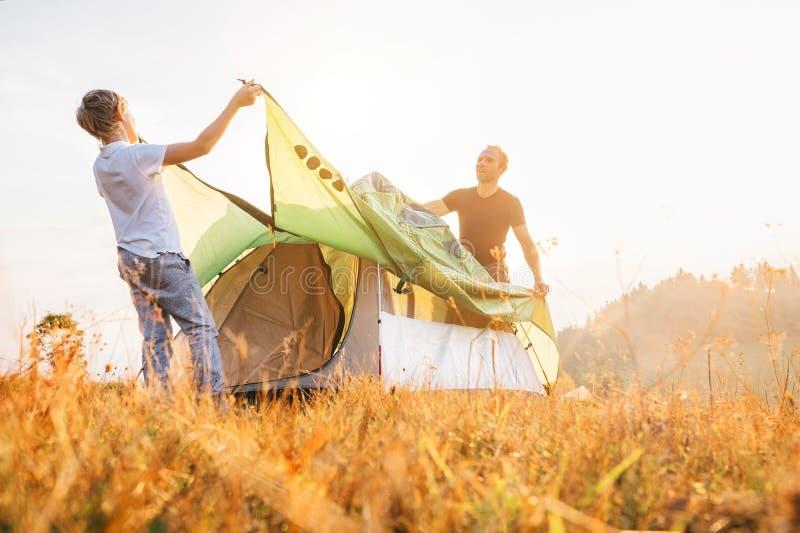 父亲和儿子在晴朗的森林沼地安装野营的帐篷 迁徙与孩子概念图象 免版税图库摄影