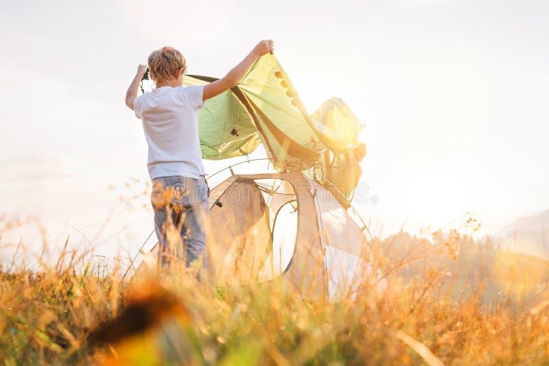 父亲和儿子在晴朗的森林沼地安装野营的帐篷 免版税图库摄影