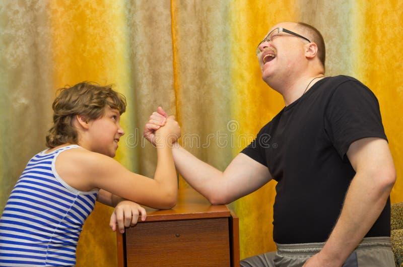 父亲和儿子在武器角力竞争 免版税库存照片