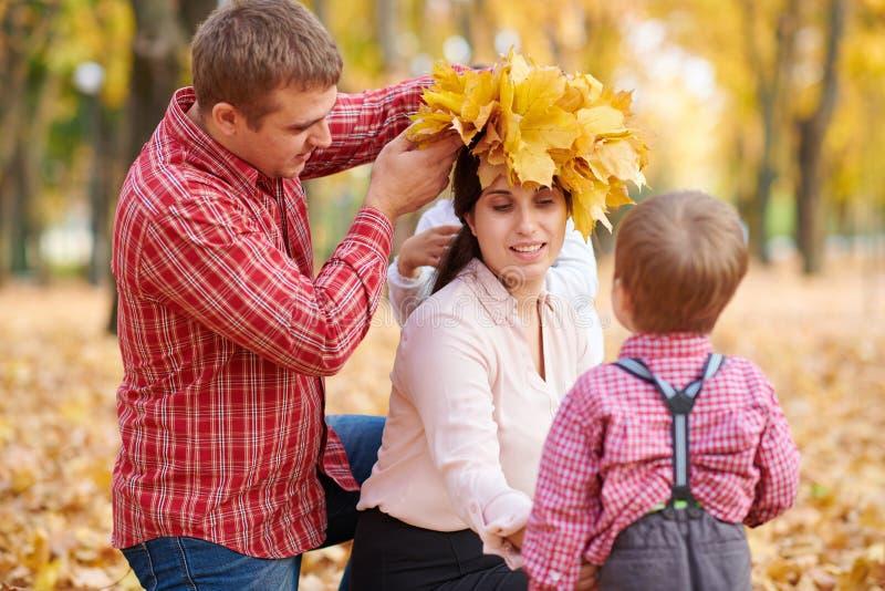 父亲和儿子在母亲头上把黄色落叶放 幸福家庭在秋天城市公园 子项和父项 他们摆在, 免版税图库摄影