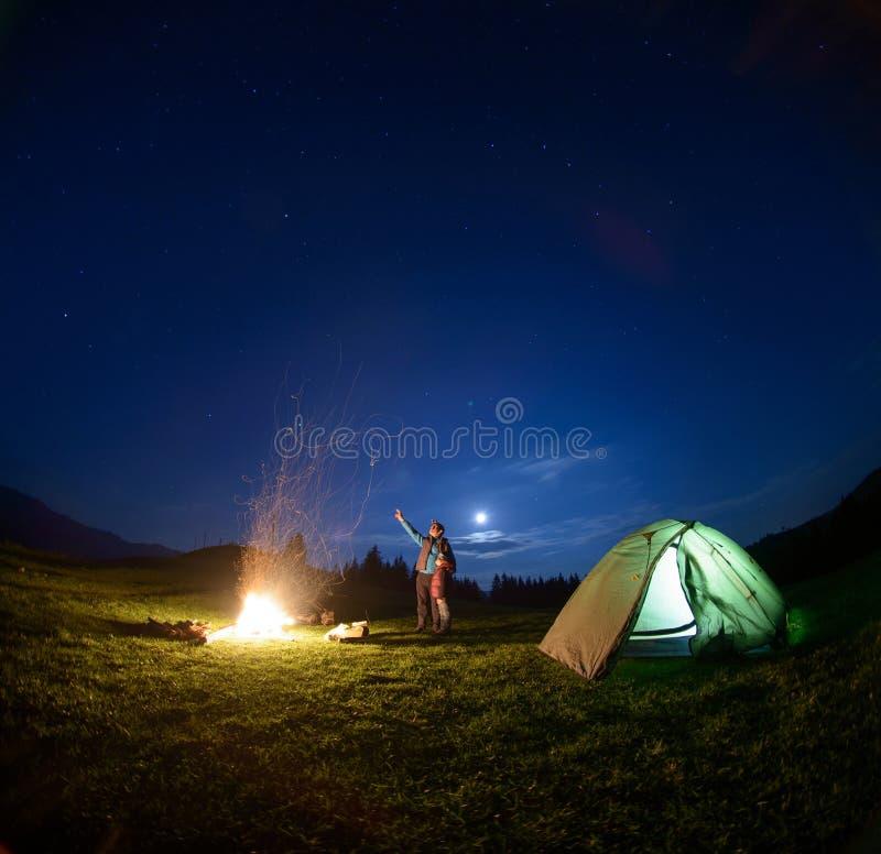 父亲和儿子在营火和帐篷附近在夜空下 库存照片