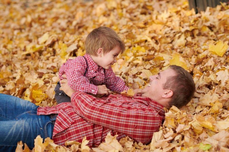 父亲和儿子在黄色叶子说谎并且在秋天城市公园获得乐趣 他们摆在,微笑,使用 明亮的黄色树 库存照片
