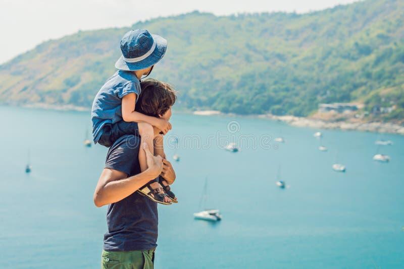 父亲和儿子在Promthep海角和Yanui背景中靠岸 普吉岛泰国 旅行与儿童概念 免版税库存照片