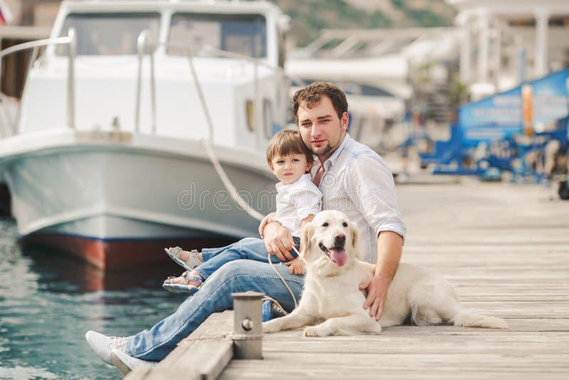 父亲和儿子坐与狗在长凳在海附近 免版税图库摄影