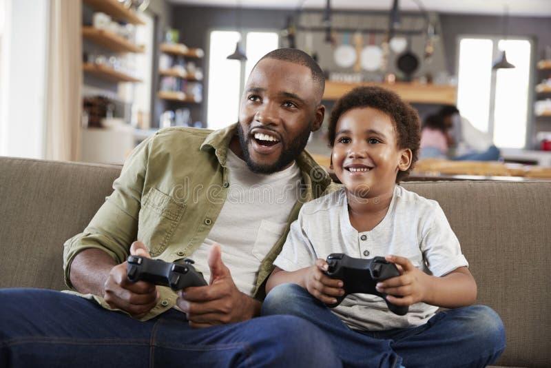 父亲和儿子坐沙发在打电子游戏的休息室 图库摄影