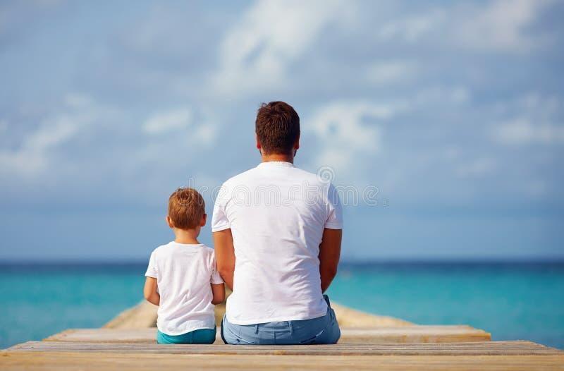 父亲和儿子坐码头在海附近 库存图片