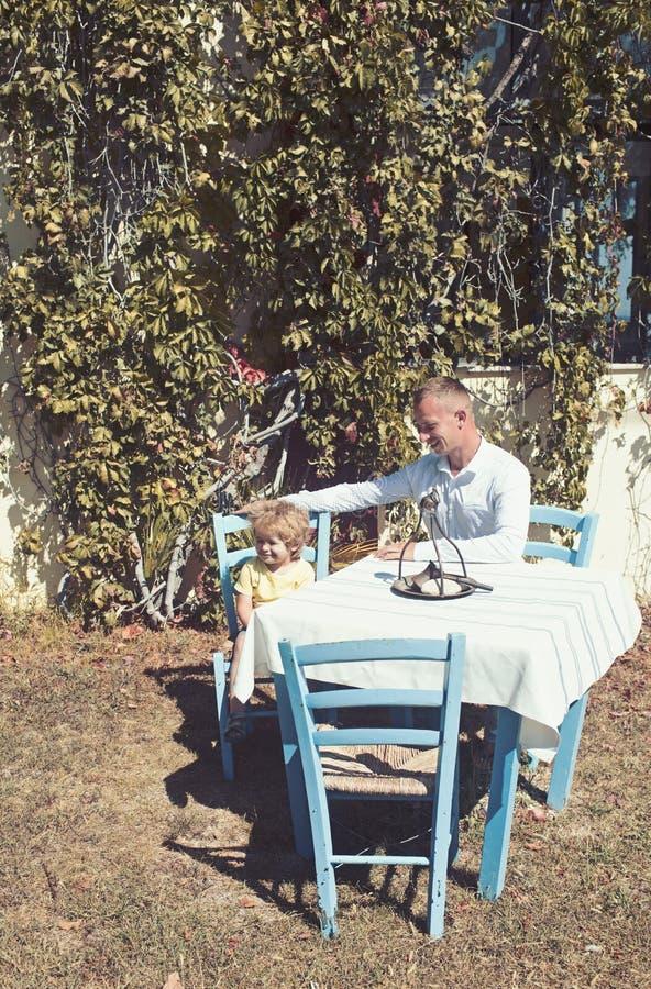 父亲和儿子室外咖啡馆的 对他的男婴的人微笑在餐馆 家族关系父母和孩子享用 免版税图库摄影