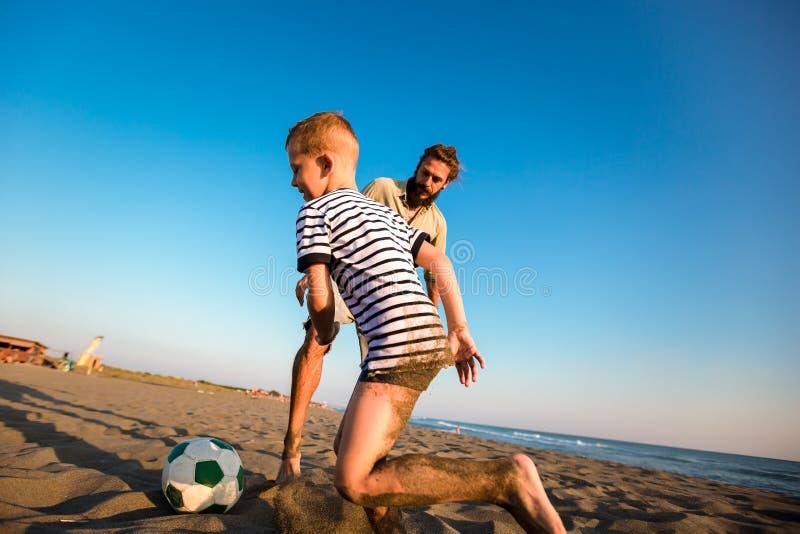 父亲和儿子戏剧足球或橄榄球在有的海滩了不起的家庭时间在度假夏天休假 免版税图库摄影