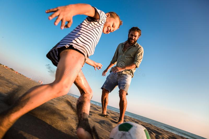父亲和儿子戏剧足球或橄榄球在有的海滩了不起的家庭时间在度假夏天休假 免版税库存照片