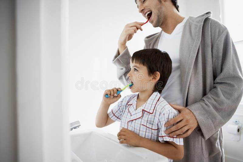 父亲和儿子掠过的牙 免版税库存照片
