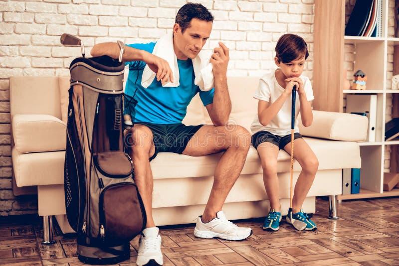 父亲和儿子有高尔夫球属性的在公寓 图库摄影