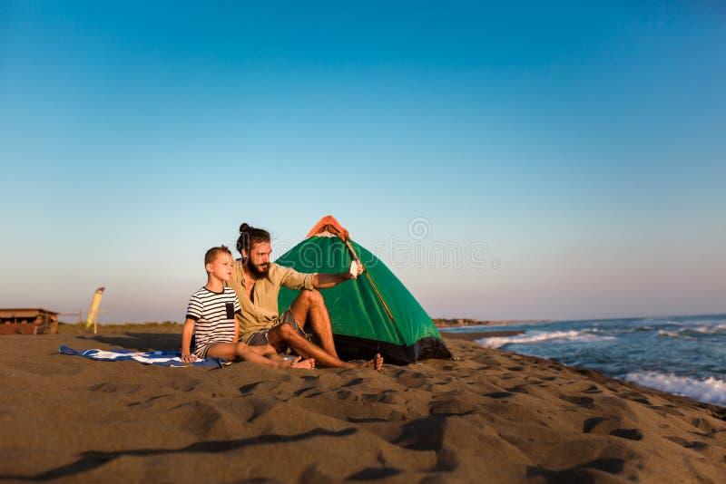 父亲和儿子海滩的使用电话 图库摄影
