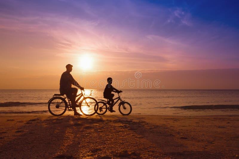 父亲和儿子海滩的在日落 免版税图库摄影