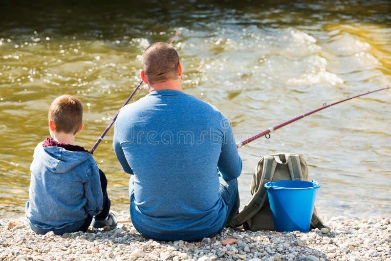 父亲和儿子渔在狂放的河 免版税库存图片