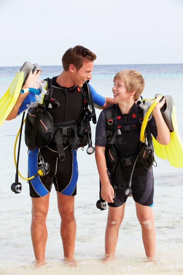 父亲和儿子用佩戴水肺的潜水设备海滩假日 库存图片