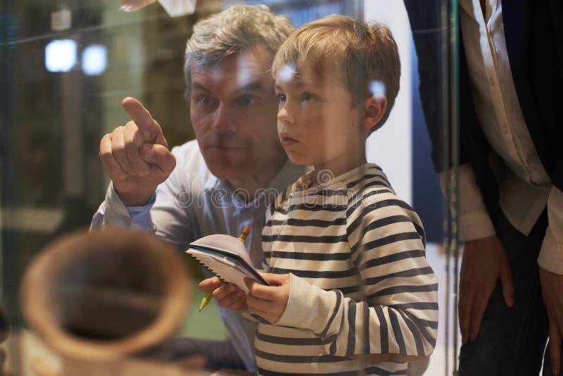 父亲和儿子看看人工制品,万一在到博物馆的旅行 免版税库存照片