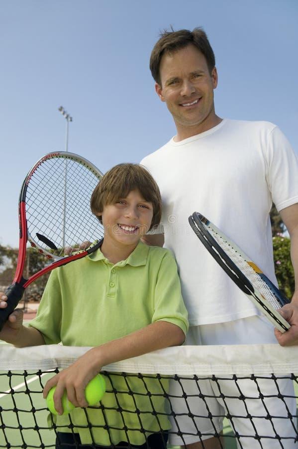 父亲和儿子网球网画象的 免版税库存照片