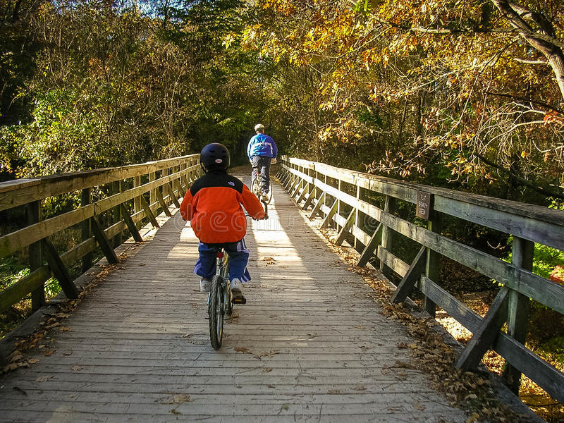 父亲和儿子自行车乘驾 免版税库存图片