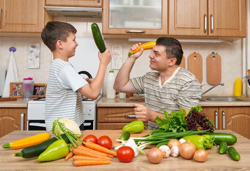 父亲和儿子获得与菜的乐趣在家庭厨房内部 人和孩子 果菜类 健康概念的食物 免版税库存照片