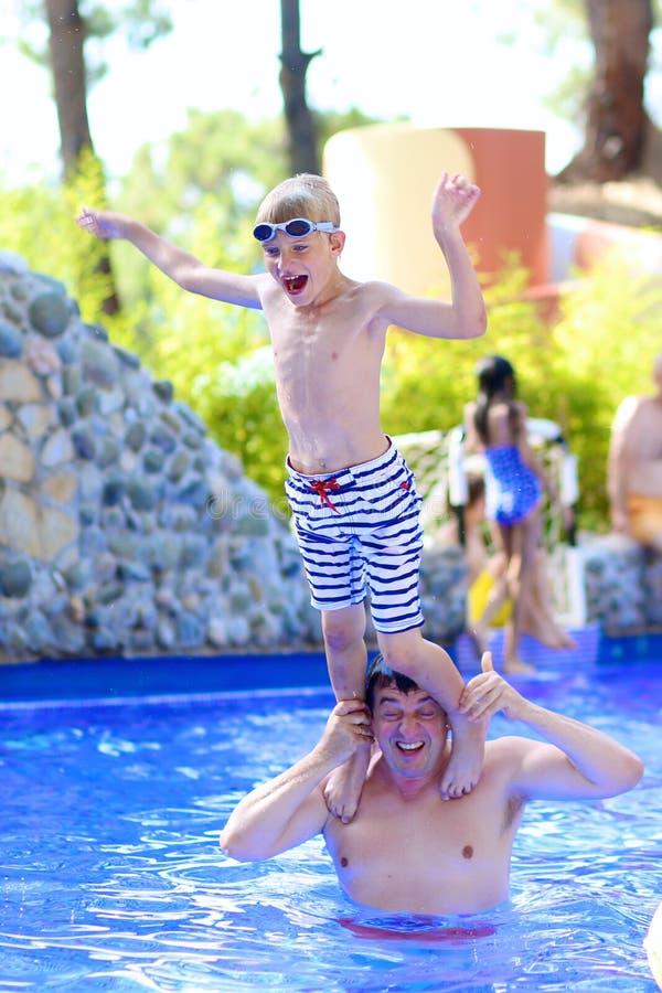 父亲和儿子获得乐趣在游泳池 库存照片