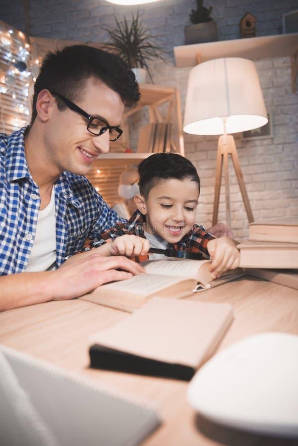 父亲和儿子读童话在家预定与放大镜在晚上 免版税库存图片