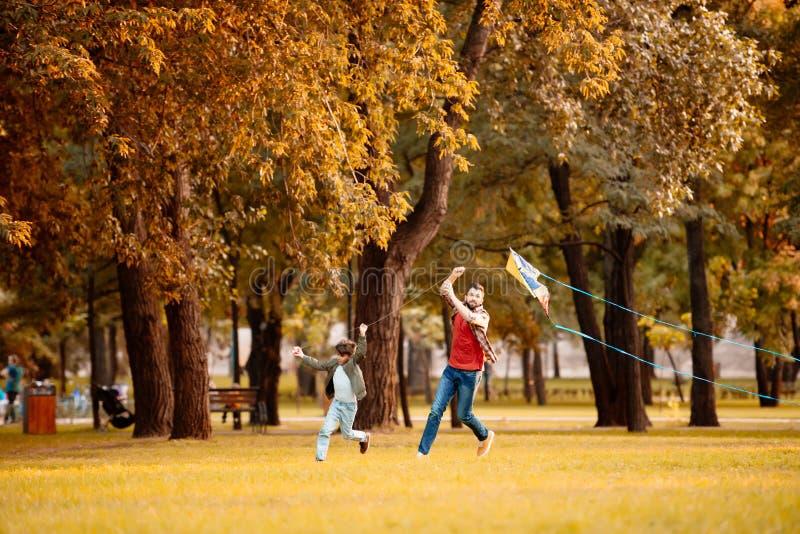 父亲和儿子赛跑,当使用与在时的一只风筝 免版税库存图片