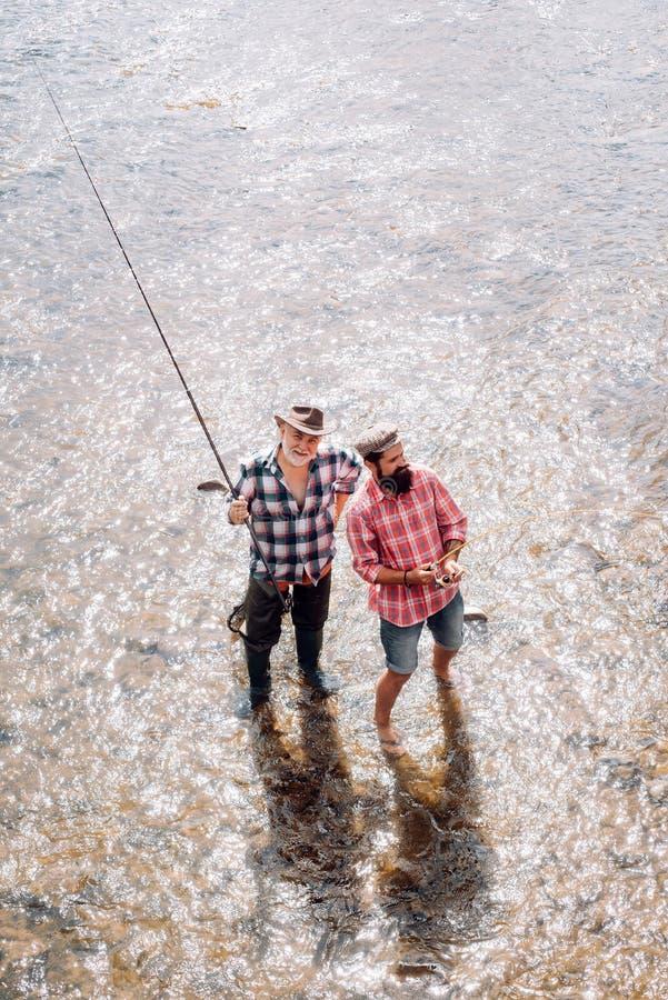 父亲和儿子钓鱼 用假蝇钓鱼是最显耀的作为捉住的鳟鱼河鳟和三文鱼一个方法 ?? 图库摄影