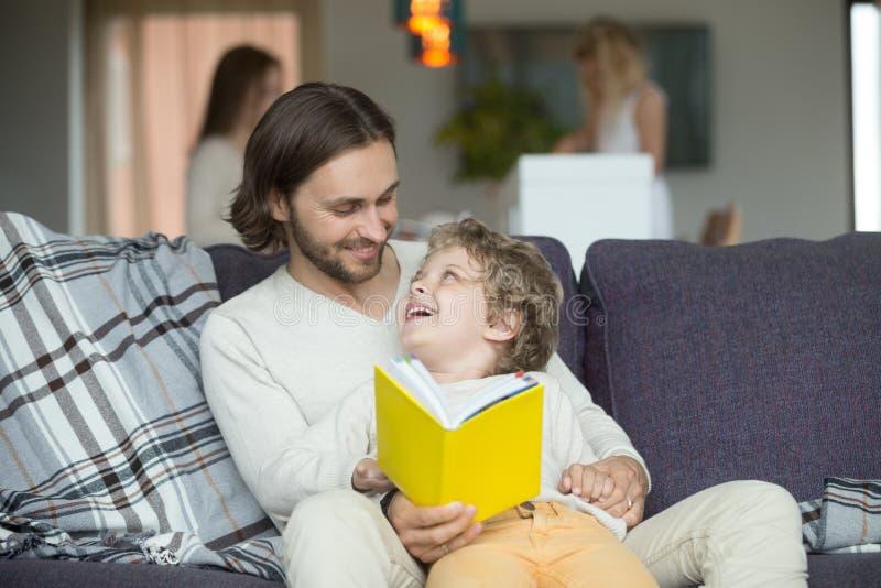父亲和儿子阅读书在家坐沙发 免版税库存图片