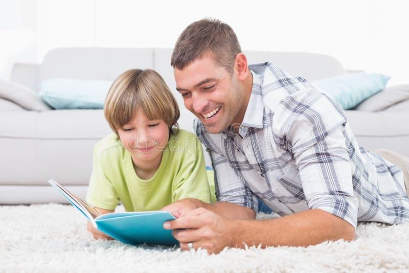 父亲和儿子阅读书,当说谎在地板上时 库存照片