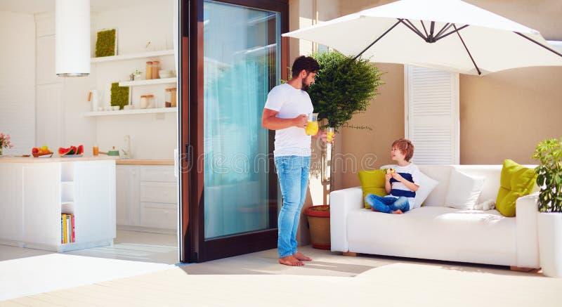 父亲和儿子,放松在有露天场所厨房的屋顶露台的家庭温暖的夏日 免版税库存图片