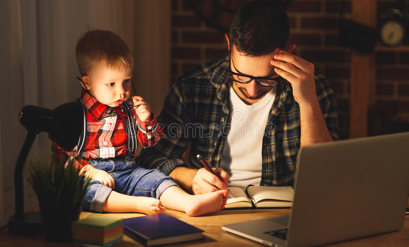 父亲和儿子婴孩在家工作在黑暗的计算机 免版税库存图片