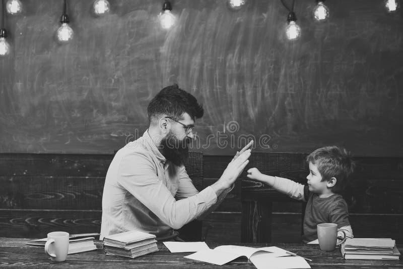 父亲和儿子 英俊的使用在教室的老师和逗人喜爱的孩子 达到任务的男小学生 冠军一点 库存照片