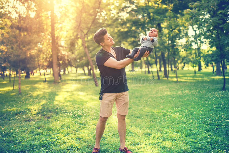 父亲和儿子画象获得乐趣在公园,抱着婴孩,婴儿的父亲 家庭天的概念在有年轻父母的公园 库存照片