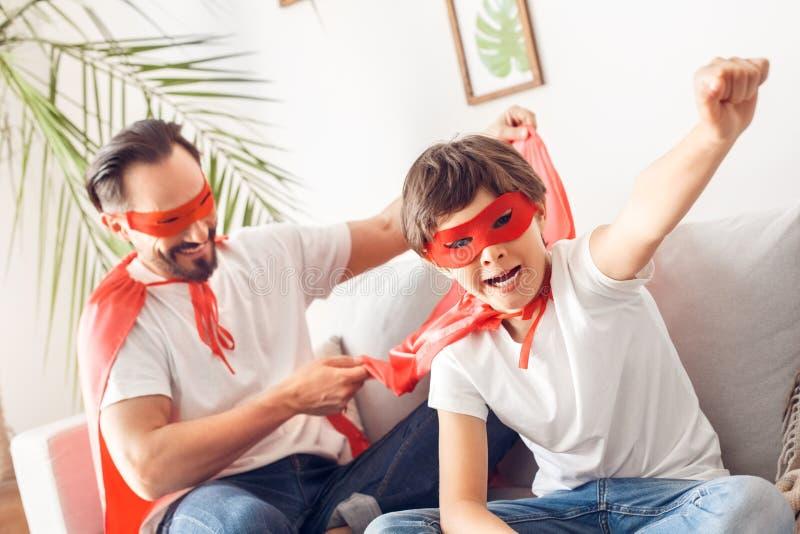 父亲和儿子superheroe服装的在家坐沙发男孩特写镜头手呼喊的有动机的一会儿爸爸藏品 免版税库存图片