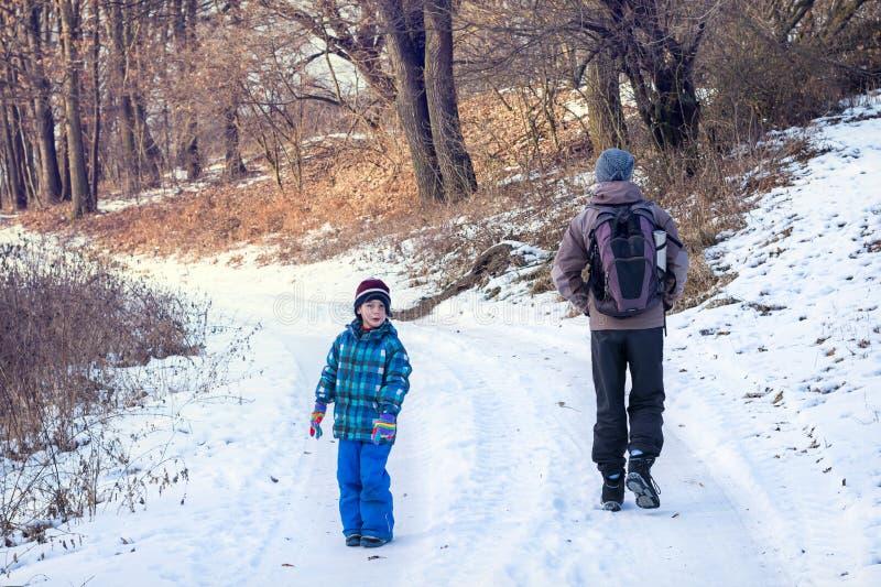 父亲和儿童走的冬天自然道路 免版税库存照片