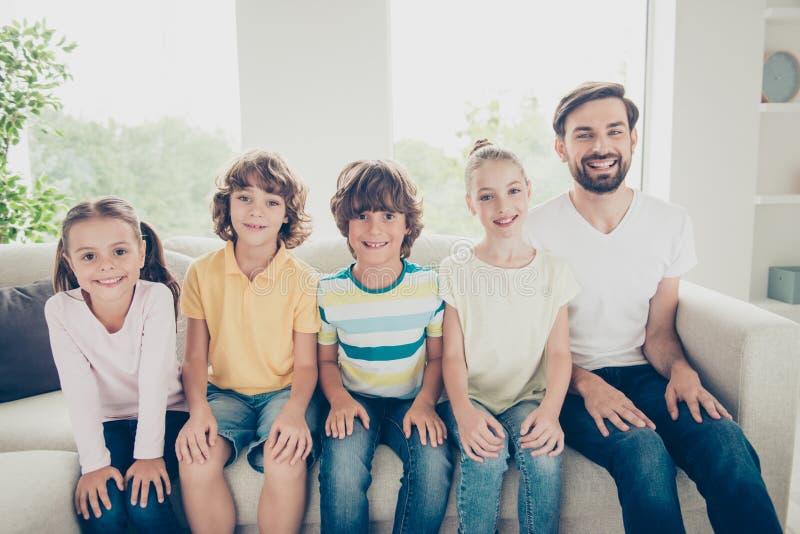 父亲和兄弟姐妹在偶然成套装备穿戴的儿童休闲坐o 库存照片