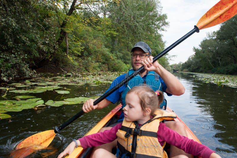 父亲和女儿一艘皮船的在水走 图库摄影