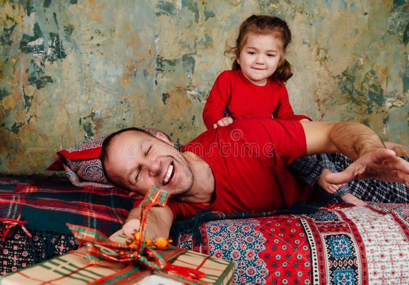 父亲和女儿为在床上的一件礼物战斗 乘坐成人的女孩设法采取礼物 库存照片