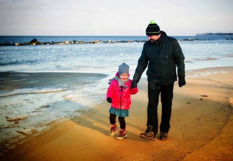 父亲和女儿冬天由海走 图库摄影