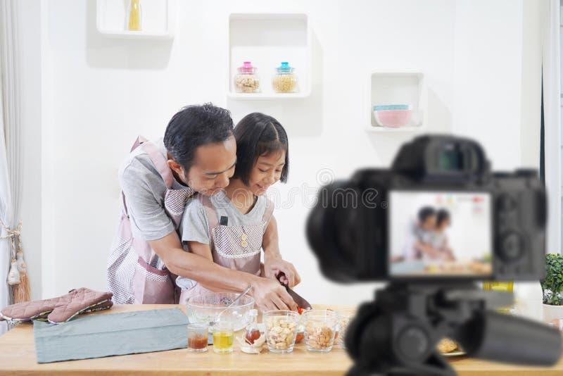 父亲和女儿厨师在家厨房里,当录音做录影 免版税图库摄影