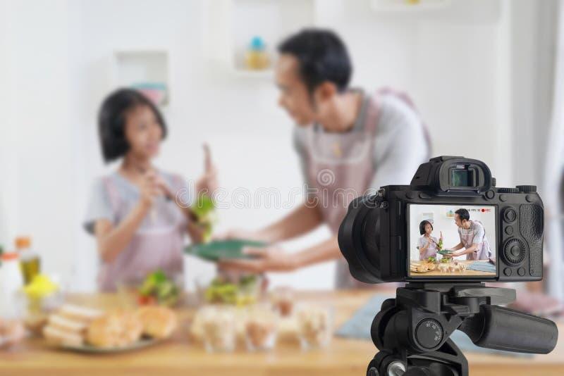 父亲和女儿厨师在家厨房里,当录音做录影 免版税库存照片