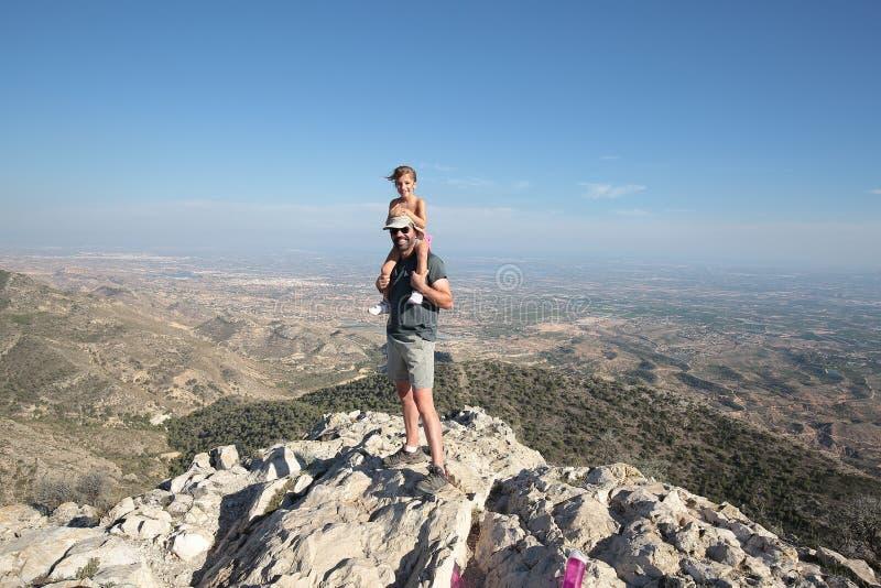 父亲和女儿在山顶部 免版税库存图片