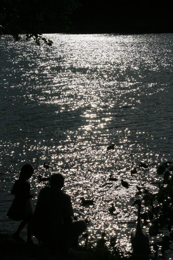 父亲和女儿在湖附近 库存图片