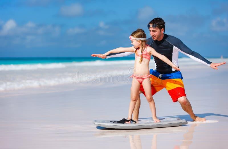 父亲和女儿实践的冲浪 免版税库存照片
