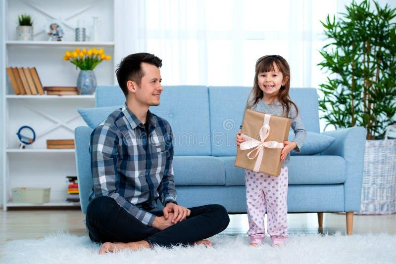 父亲和女儿或者兄弟和姐妹有一件礼物的在屋子内部 父亲节假日概念,儿童节 免版税库存图片