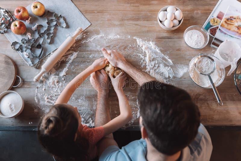 父亲和女儿揉的面团在厨房用桌上 免版税图库摄影