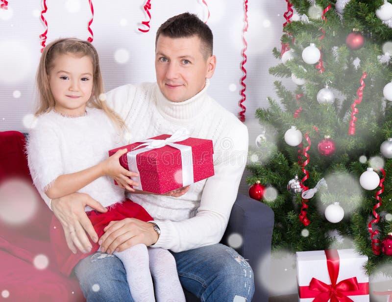 父亲和女儿有礼物的在圣诞树前面 库存图片